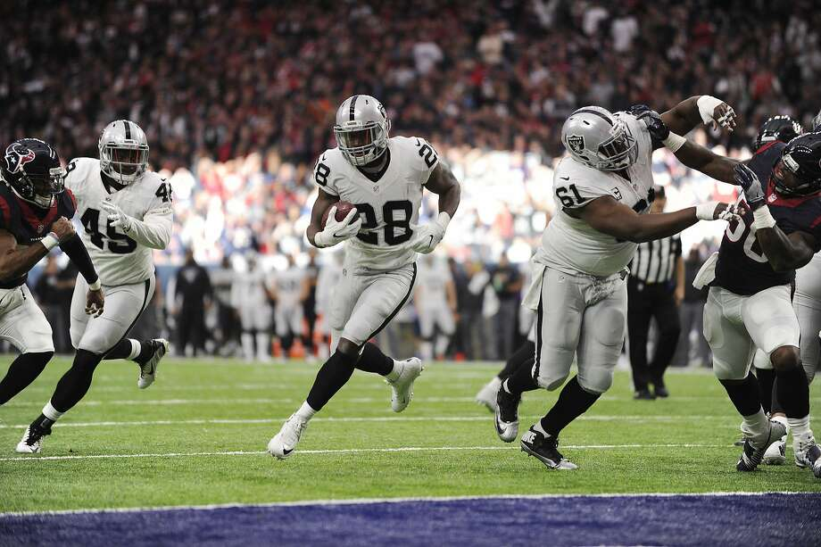 Oakland Raiders running back Latavius Murray (28) moves through a hole on the line against the Houston Texans during the first half of an AFC Wild Card NFL game Saturday, Jan. 7, 2017, in Houston. Murray scored a touchdown on the play. (AP Photo/Eric Christian Smith) Photo: Eric Christian Smith, Associated Press