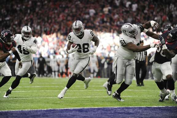 Oakland Raiders running back Latavius Murray (28) moves through a hole on the line against the Houston Texans during the first half of an AFC Wild Card NFL game Saturday, Jan. 7, 2017, in Houston. Murray scored a touchdown on the play. (AP Photo/Eric Christian Smith)