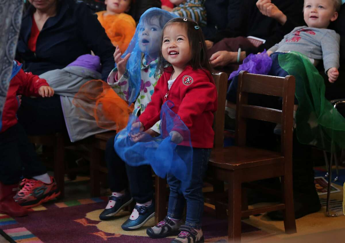 Two-year-old Jiana Chung Yan (in red) and behind her Delphine Magini, age 2, listen in to a book reading at the West Portal Branch of the San Francisco Public Library on Tuesday, Jan. 10, 2017 in San Francisco, Calif. Through the new program