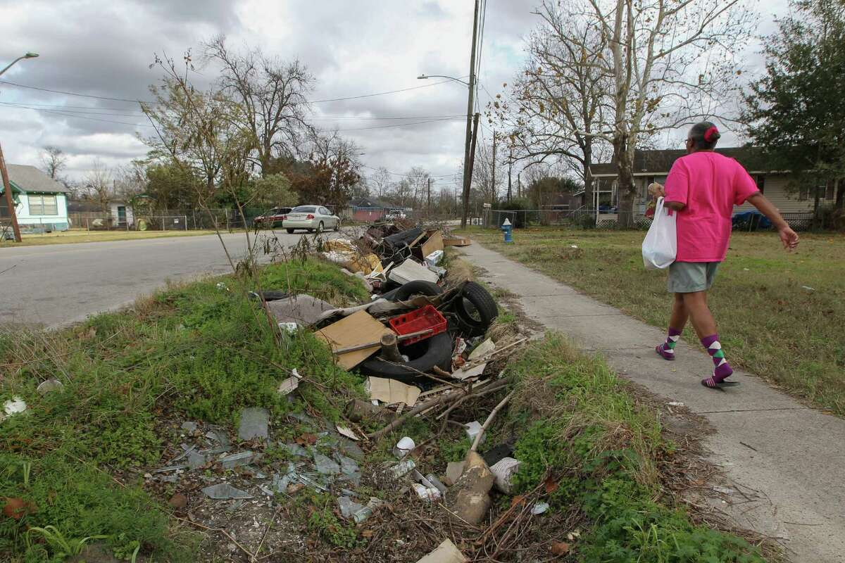 A woman walks passed a mound of ditch debris in Houston near Collingsworth Street and Lockwood Drive on Tuesday. Mayor Sylvester Turner is seeking $10 million towards small emergency drainage repair. Ditches full of debris can cause drainage issue.