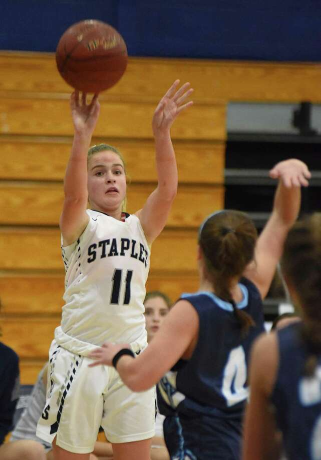 Staples guard Elle Fair puts up a shot over Wilton's Meaghan Downey during Tuesday's FCIAC girls basketball game in Westport. Staples won the game 45-44 in overtime. Photo: John Nash / Hearst Connecticut Media / Norwalk Hour