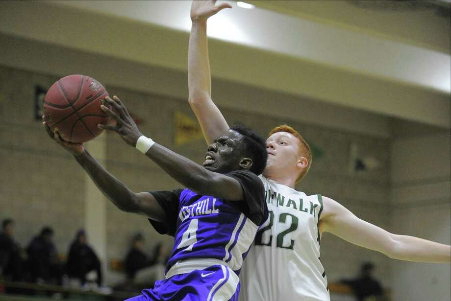 Westhill Tariks Rivers lays in a shot under pressure from Norwalk Hugh Clyne in a FCIAC boys basketball game at Norwalk High School on Jan. 10, 2017. Photo: Matthew Brown / Hearst Connecticut Media / Stamford Advocate