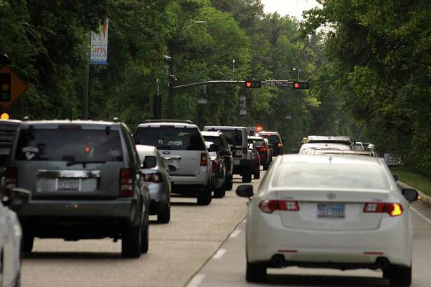 Evening commuters wait at a signal light as they make their way home on the Woodlands Parkway. Photograph by David Hopper