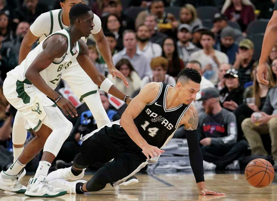 San Antonio Spurs guard Danny Green (14) falls as he chases the ball next to Milwaukee Bucks guard Tony Snell during the first half of an NBA basketball game, Friday, Nov. 10, 2017, in San Antonio. (AP Photo/Darren Abate) Photo: Darren Abate, Associated Press / FR115 AP