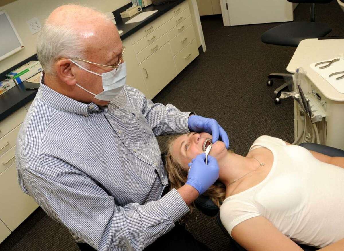 Orthodontist Allan Phillips prepares to remove the braces from 14-year-old Kiki Melanophy's teeth at his office in Brookfield on Tuesday May 25,2010.