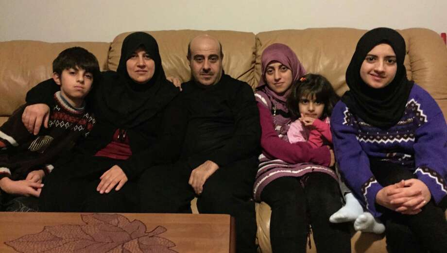 The Albakour family, Syrian refugees, in their Watervliet apartment. From left, Rasheed, 12; Eshraq, the mother; Subhi, the father; Nehla, 24 (holding Sidra, 6); and Duaa, 15. (Paul Grondahl / Times Union)