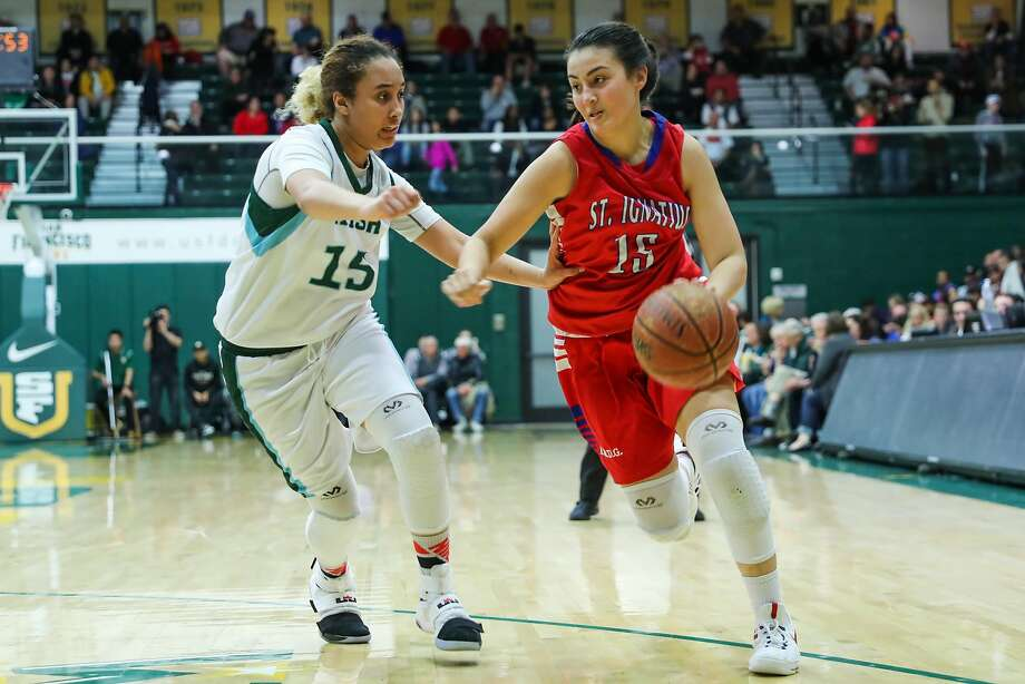 St.Ignacius player Alyssa Downs (#15) drives the ball past Sacred Heart player Errayanna Hartfield (#15, left)  during a game between Sacred Heart Cathedral and St. Ignatius at War Memorial gymnasium in San Francisco, Calif., on Tuesday, Jan. 10, 2017. Photo: Gabrielle Lurie, The Chronicle