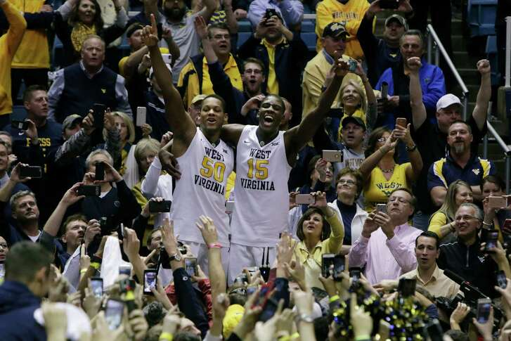 West Virginia forward Sagaba Konate (50) and West Virginia forward Lamont West (15) celebrate their win at the conclusion of an NCAA college basketball game against Baylor, Tuesday, Jan. 10, 2017, in Morgantown, W.Va. West Virginia defeated Baylor 89-68. (AP Photo/Raymond Thompson)