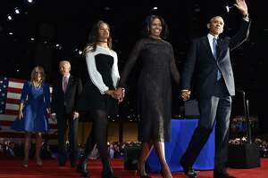 US First Lady Michelle Obama (2R) and US President Barack Obama greet supporters as daughter Malia looks on after the President delivered his farewell address in Chicago, Illinois on January 10, 2017. Barack Obama closes the book on his presidency, with a farewell speech in Chicago that will try to lift supporters shaken by Donald Trump's shock election. / AFP PHOTO / Nicholas KammNICHOLAS KAMM/AFP/Getty Images