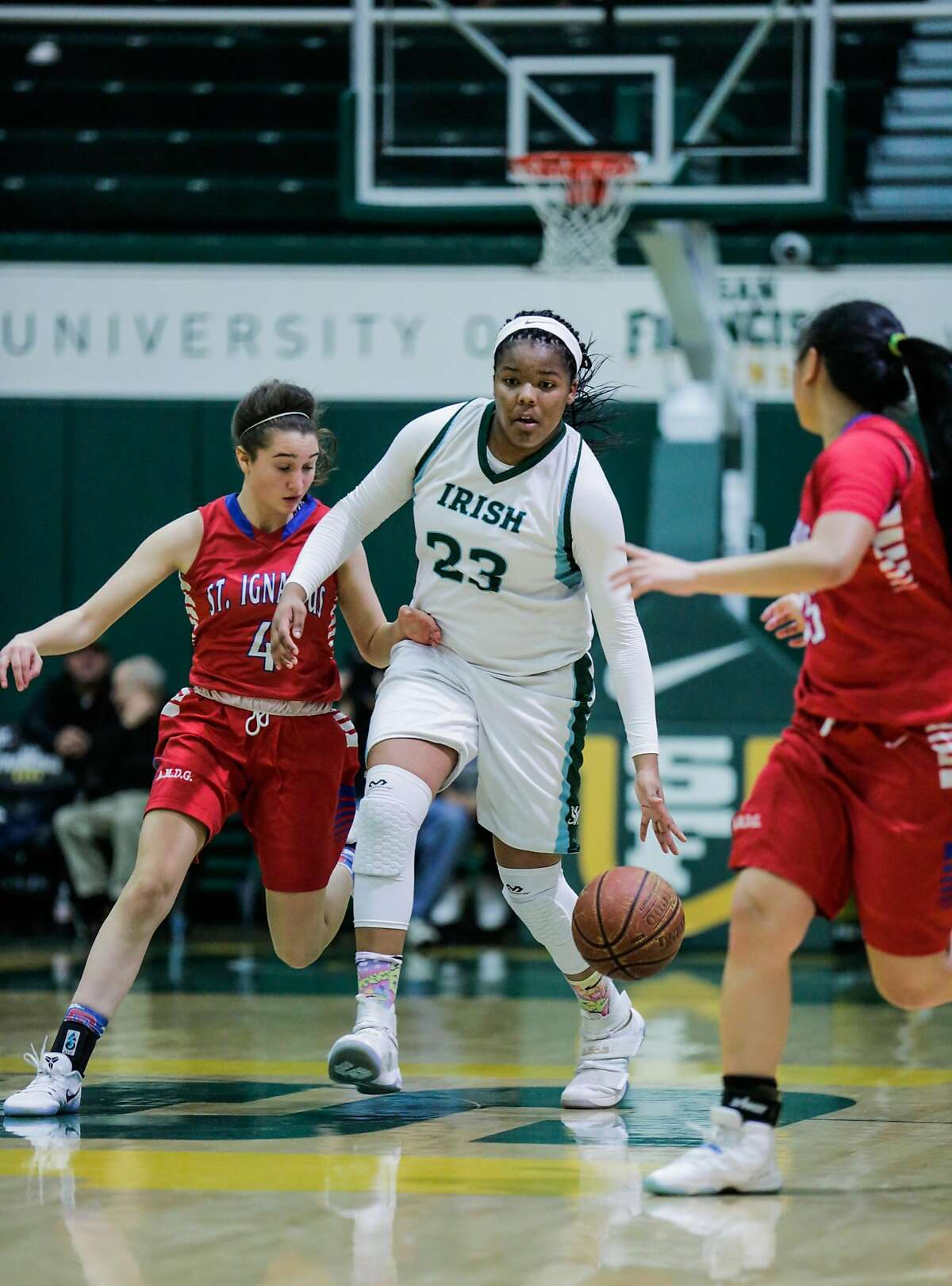 Sacred Heart player IImar'l Thomas (#23) drives the ball past St. Ignacius player Rachel Harvey (#4)during a game between Sacred Heart Cathedral and St. Ignatius at War Memorial gymnasium in San Francisco, Calif., on Tuesday, Jan. 10, 2017.