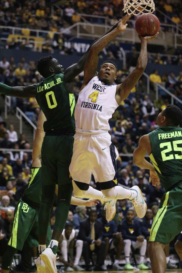 West Virginia guard Daxter Miles Jr. (4) shoots the ball as Baylor forward Jo Lual-Acuil Jr. (0) attempts to block his shot during the second half of an NCAA college basketball game, Tuesday, Jan. 10, 2017, in Morgantown, W.Va. (AP Photo/Raymond Thompson) ORG XMIT: WVRT111 Photo: Ray Thompson / FR171247 AP