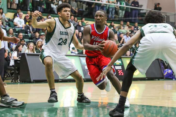 St.Ignacius player Darrion Trammell (#15, center) drives the ball past Sacred Heart player Nathan Robinson (#24) during a game between Sacred Heart Cathedral and St. Ignatius at War Memorial gymnasium in San Francisco, Calif., on Tuesday, Jan. 10, 2017.
