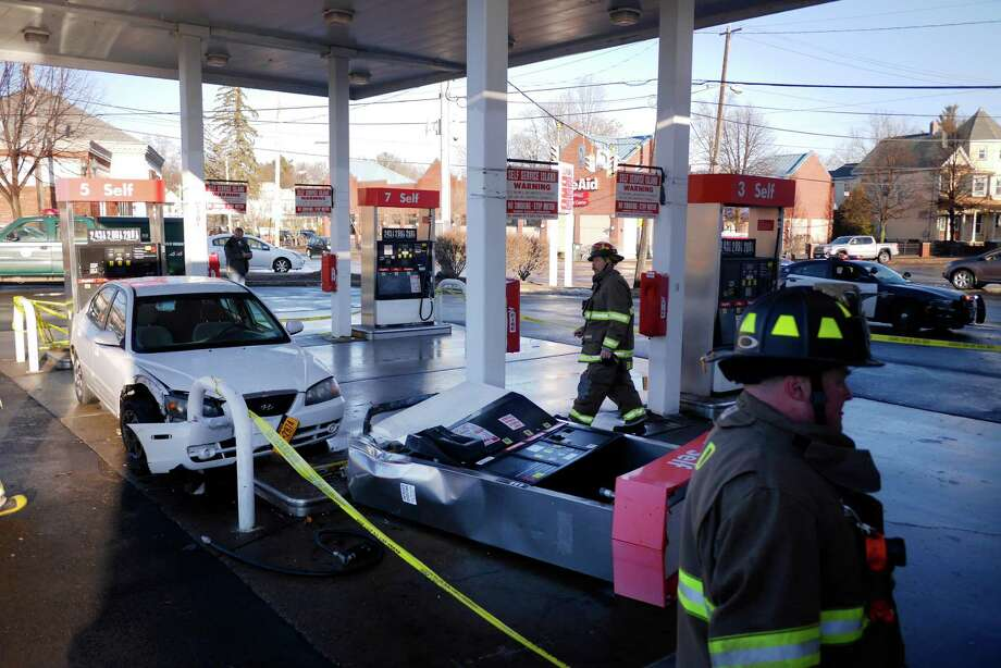 Schenectady firefighters work at the scene of a car accident at the LukOil gas station at the corner of McClellan Street and Eastern Parkway on Wednesday, Jan. 11, 2017, in Schenectady, N.Y.  The vehicle was being driven on McClellan going towards Eastern when it left the road and crashed into a gas pump at the station.  Icy road conditions may have been a factor in the crash. (Paul Buckowski / Times Union) Photo: STAFF / 20039408A