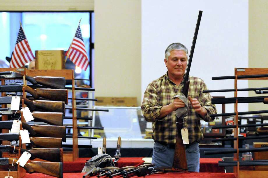 Mike Worth of Wilton wipes down a gun while setting up the Fire Tower Doubles booth at the New York Gun and Militaria Show on Friday Jan. 29, 2016 in Saratoga Springs, N.Y. (Michael P. Farrell/Times Union) Photo: Michael P. Farrell / 10035174A