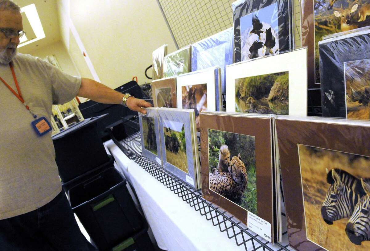 Wildlife photographer Dennis Donohue sets up his booth at the New York Gun and Militaria Show on Friday Jan. 29, 2016 in Saratoga Springs, N.Y. (Michael P. Farrell/Times Union)