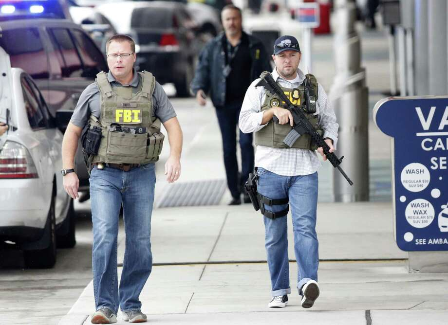 FBI agents walk outside the terminal at Fort Lauderdale–Hollywood International Airport, Friday, Jan. 6, 2017, in Fort Lauderdale, Fla. A gunman opened fire in the baggage claim area at the airport Friday, killing several people and wounding others before being taken into custody in an attack that sent panicked passengers running out of the terminal and onto the tarmac, authorities said. (AP Photo/Wilfredo Lee) Photo: Wilfredo Lee, STF / Associated Press / Copyright 2017 The Associated Press. All rights reserved.
