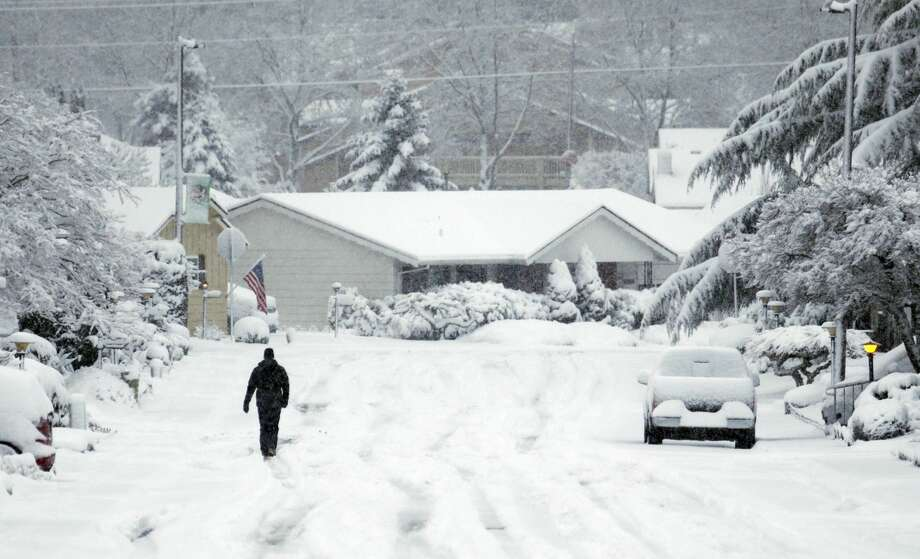 A lone figure walks down a snow covered street in King City, Ore., Wednesday, Jan. 11, 2017. A major snowstorm spread through Portland and parts of Washington state overnight, toppling trees, closing schools and cutting power to thousands.(AP Photo/Don Ryan) Photo: Don Ryan/AP