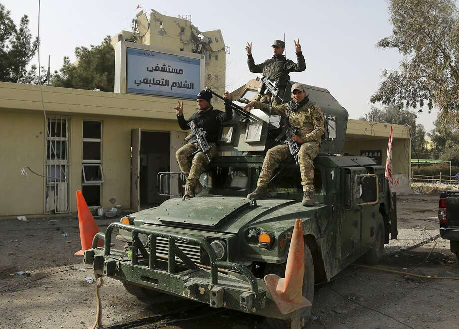 Iraqi security forces flash the victory sign outside Mosul's al-Salam hospital, which was badly damaged in the battle to retake it from Islamic State militants. Photo: Khalid Mohammed, Associated Press