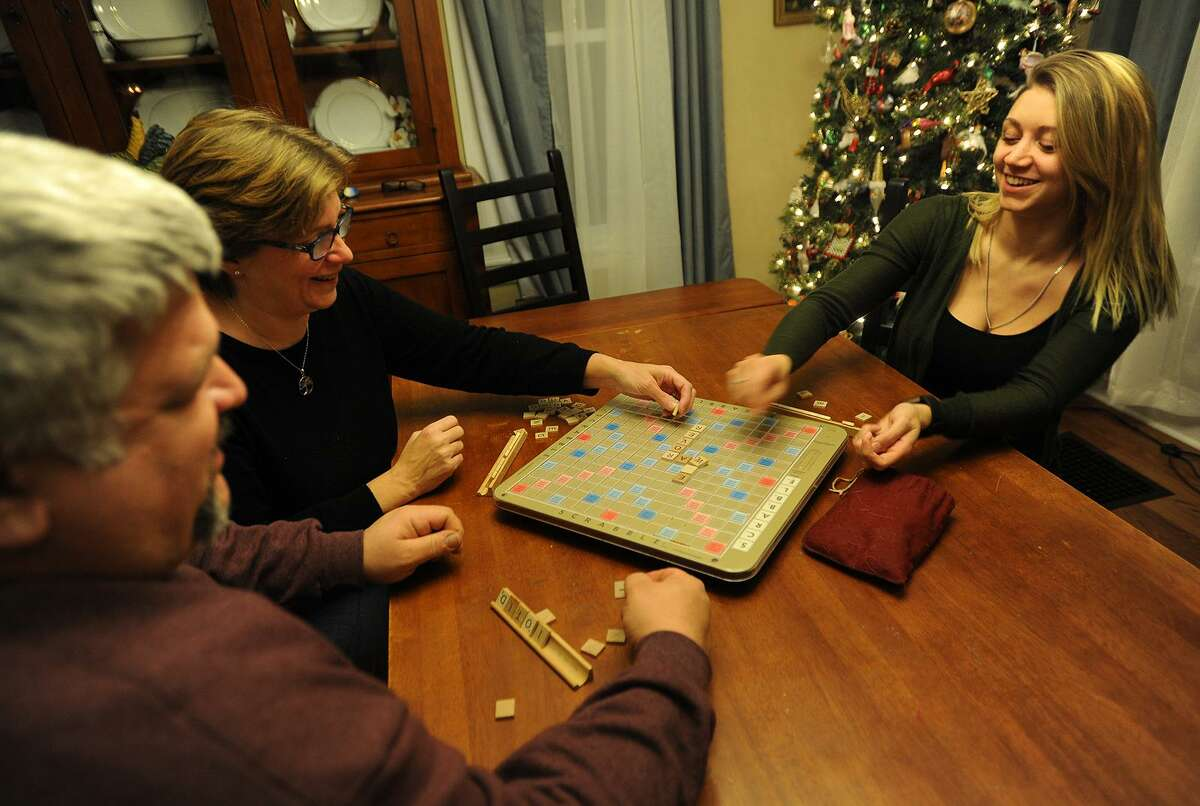 Alexandra Pisco, 23, right, plays a game of Scrabble with her parents Rich and Wendy DiCarlo at their home in Derby, Conn. on Monday, January 9, 2017. Pisco, who graduated two years ago from the University of Bridgeport, plans to pursue a career as a police officer.