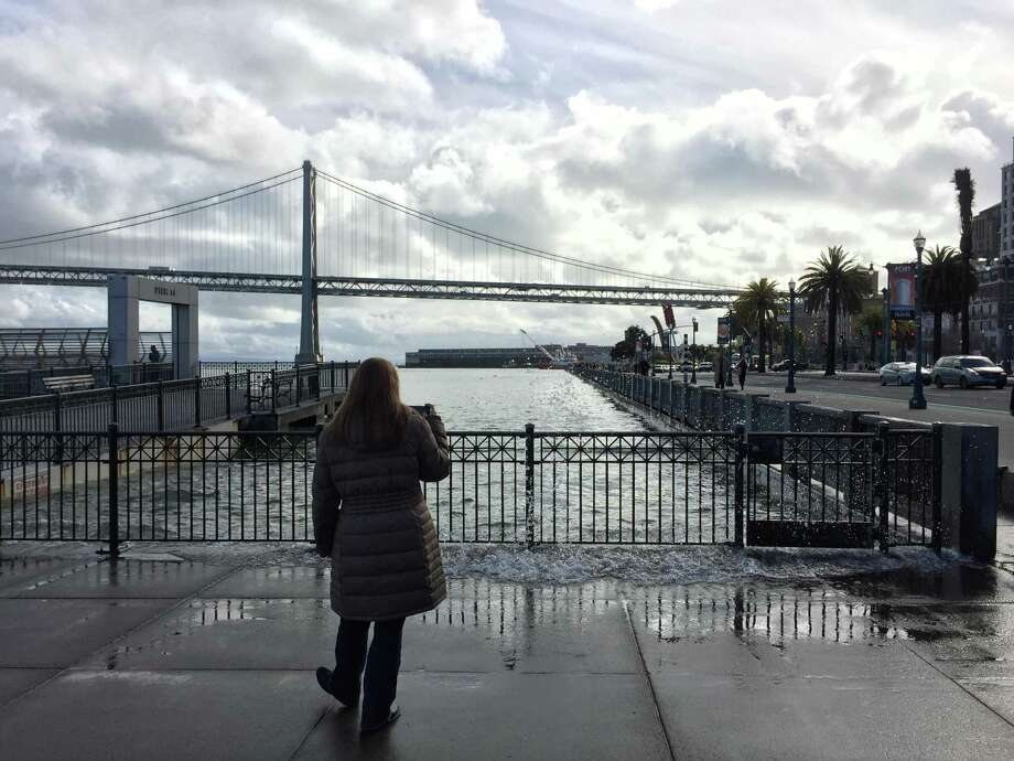 Pittsburg resident Tracy DePiero, 43, stops by the Embarcadero on Wednesday to take a picture of the king tides. Photo: Sarah Ravani / /