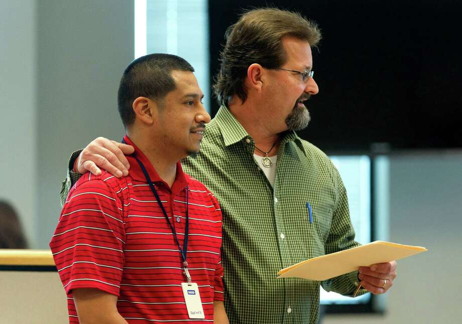 Miguel Sanchez, left, is seen along side Juvenile Probation Director Bruce Gusler as Sanchez is presented with the Montgomery County Employee of the Month award during Montgomery County Commissioners Court at Alan B. Sadler Commissioners Court Building Tuesday, Jan. 10, 2017, in Conroe. Photo: Jason Fochtman, Staff Photographer / Houston Chronicle