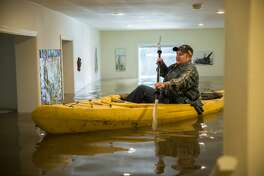 Lorin Doeleman uses a kayak to check her flooded home on Wednesday, Jan. 11, 2017 in Guerneville, Calif. She is moving her belongings to her Sacramento home.