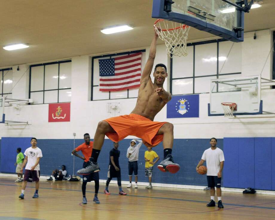 Joey Wallace, 18, playfully dangles from a basketball hoop at the War Memorial in Danbury, Conn., Tuesday afternoon, June 2, 2015. Joey, a  varsity player on Immaculate High School's team and his friends meet every day after school to play pick-up basketball. Graduation is Wednesday night. Photo: Carol Kaliff / Carol Kaliff / The News-Times