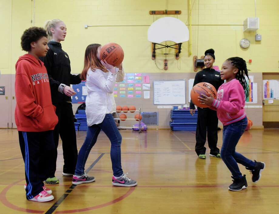 Siena women's basketball players, Anna Lundquist, left, and Deja Rawls, right, work with students at Yates Elementary School as they shoot baskets in the gym on Wednesday, Jan. 11, 2017, in Schenectady, N.Y.  The Siena students were at the school as part of the annual Saints in the Community Adopt-A-School program.  The Siena athletes spoke to the children about hard work, commitment, and making healthy life choices.   (Paul Buckowski / Times Union) Photo: PAUL BUCKOWSKI / 20039403A