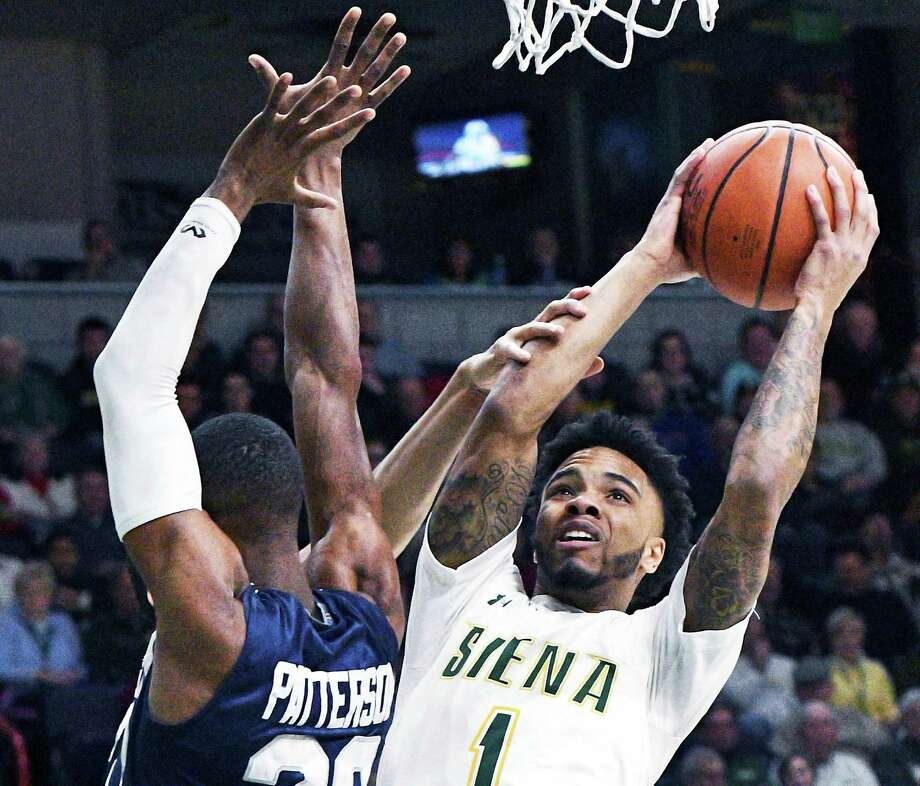 Siena's #1 Marquis Wright, right, goes to the basket as Saint Peter's #20 Chazz Patterson defends during Saturday's game at the Times Union Center Jan. 7, 2017 in Albany, NY.  (John Carl D'Annibale / Times Union) Photo: John Carl D'Annibale / 20039264A
