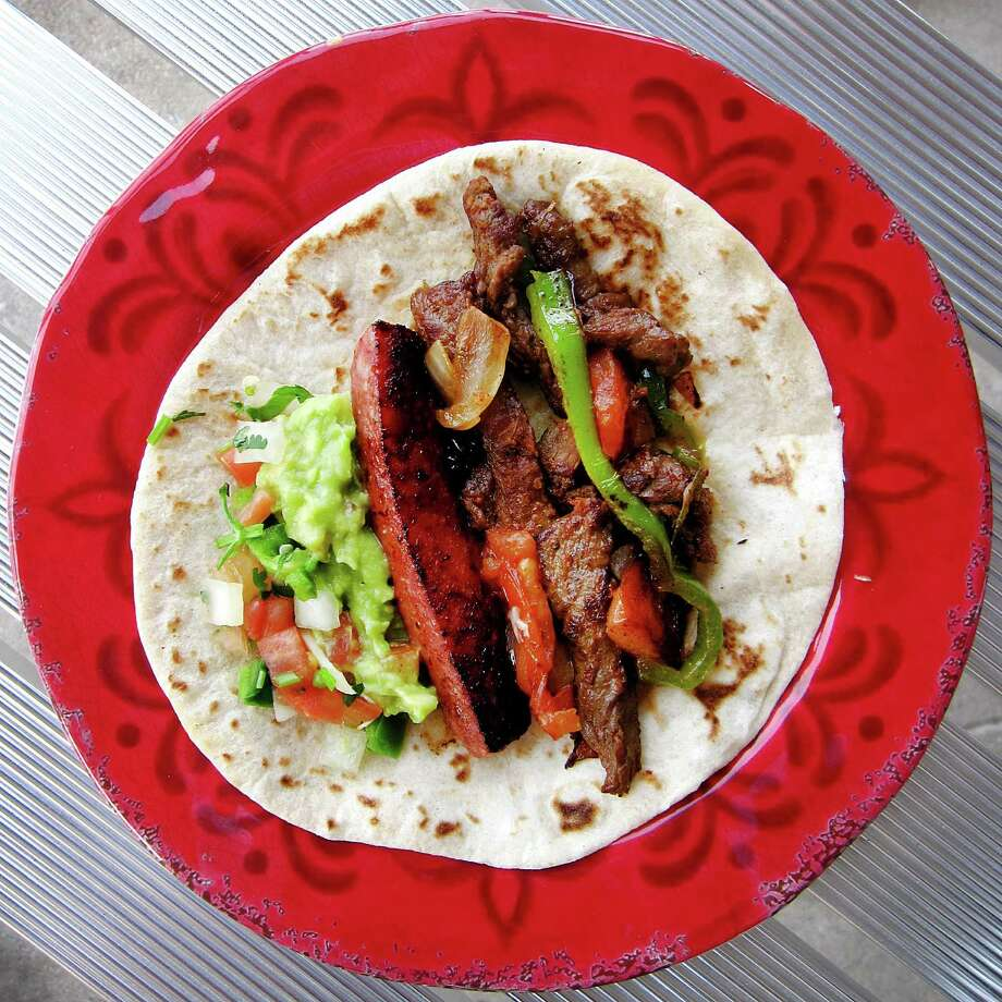 A taco compiled from the Fajita a la Plancha platter, with beef fajita, sausage, peppers and onions on a handmade flour tortilla from Lindo Jalisco Grill on Fredericksburg Road. Photo: Mike Sutter /San Antonio Express-News