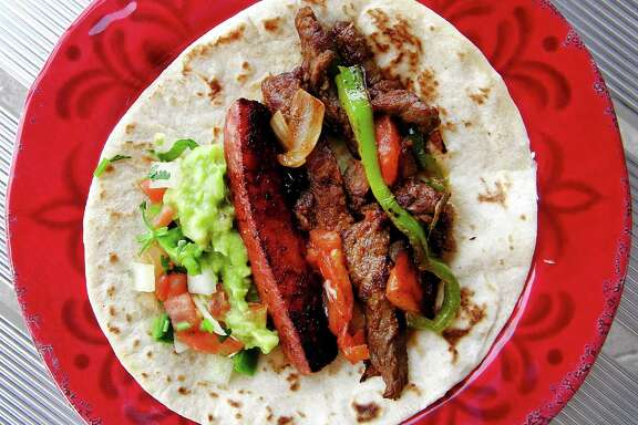 A taco compiled from the Fajita a la plancha platter, with beef fajita, sausage, peppers and onions on a handmade flour tortilla from Lindo Jalisco Grill on Fredericksburg Road.