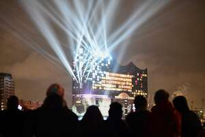 "People watch the opening light show of the Elbphilharmonie concert hall in Hamburg, northern Germany, on January 11, 2017. Around nine and a half years after laying the foundation stone, the new concert house nicknamed ""Elphi"" and sitting ontop of an old warehouse building will have its gala opening on January 11, 2017. / AFP PHOTO / Tobias SCHWARZTOBIAS SCHWARZ/AFP/Getty Images"