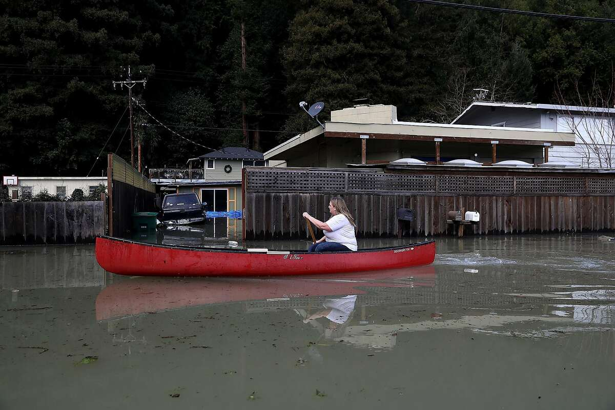 A resident named Kayte paddles her canoe through floodwaters on January 11, 2017 in Guerneville, California. A new round of storms are bringing heavy rains and flooding to Northern California just days after rain and snow storms pounded the region bringing much needed water to drought stricken California. (Photo by Justin Sullivan/Getty Images)