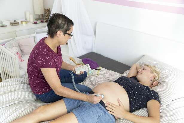 A midwife examines a pregnant woman who is in the 9th month in Berlin Schöneberg with a Doppler fetal monitor to listen to the  heartbeat of the unborn by ultrasound. 