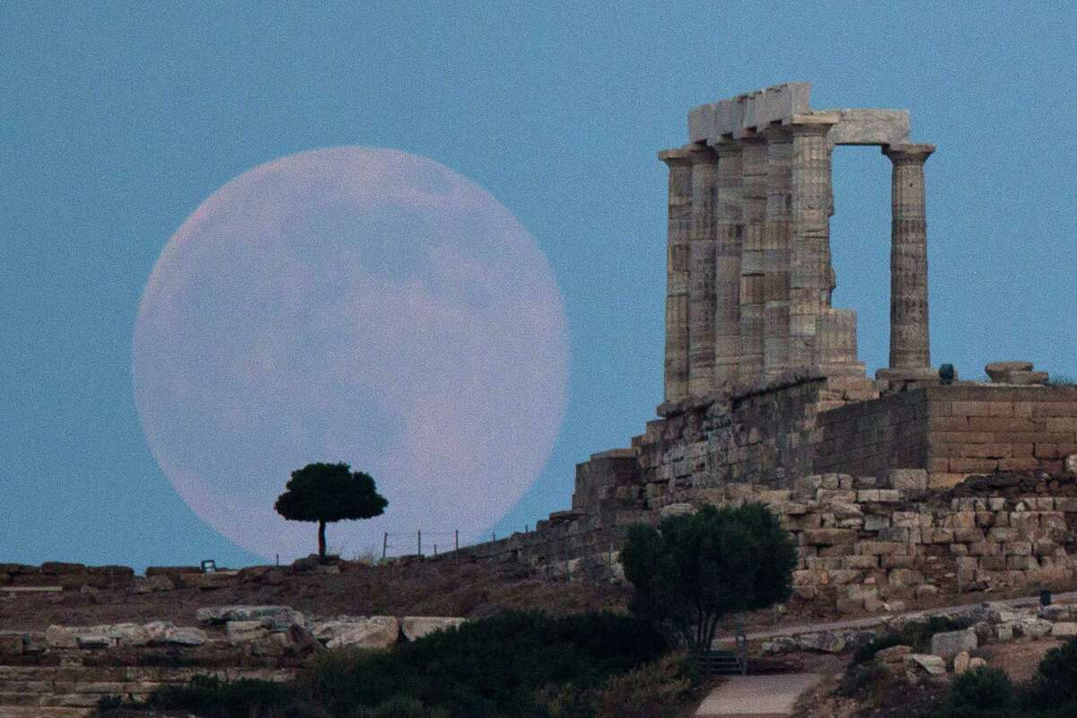 FILE - In this June 20, 2016 file photo, the full moon rises behind a tree next to the ruins of the ancient marble Temple of Poseidon, built in 444 BC, at Cape Sounion, southeast of Athens, on the eve of the summer solstice. On Wednesday, Jan. 11, 2017, a California-led research team reported that the moon formed within 60 million years of the birth of the solar system. Previous estimates ranged within 100 million years, all the way out to 200 million years of the solar systemÂ?'s creation. (AP Photo/Petros Giannakouris)