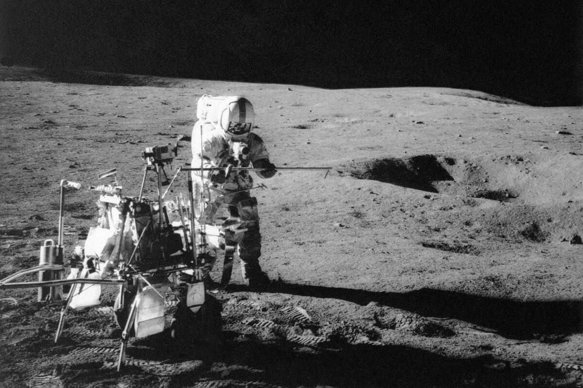 FILE - In this Feb. 13, 1971 file photo, Apollo 14 astronaut Alan B. Shepard Jr. conducts an experiment near a lunar crater, using an instrument from a two-wheeled cart carrying various tools. On Wednesday, Jan. 11, 2017, a California-led research team reported that the moon formed within 60 million years of the birth of the solar system. Previous estimates ranged within 100 million years, all the way out to 200 million years of the solar systemÂ?'s creation. (NASA via AP)