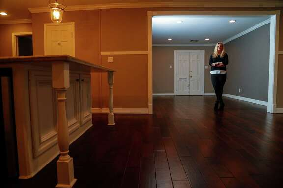 Shannon Bedinger stands in the empty living room of her home that has been on the market for the last six months, Wednesday, January 11, 2017.  The Bedingers own a house in a sought-after neighborhood zoned to some of the best schools in Houston. They put their house on the market almost six months ago expecting to sell it in a reasonable amount of time. Almost six months later it still hasn't sold.  ( Karen Warren / Houston Chronicle )