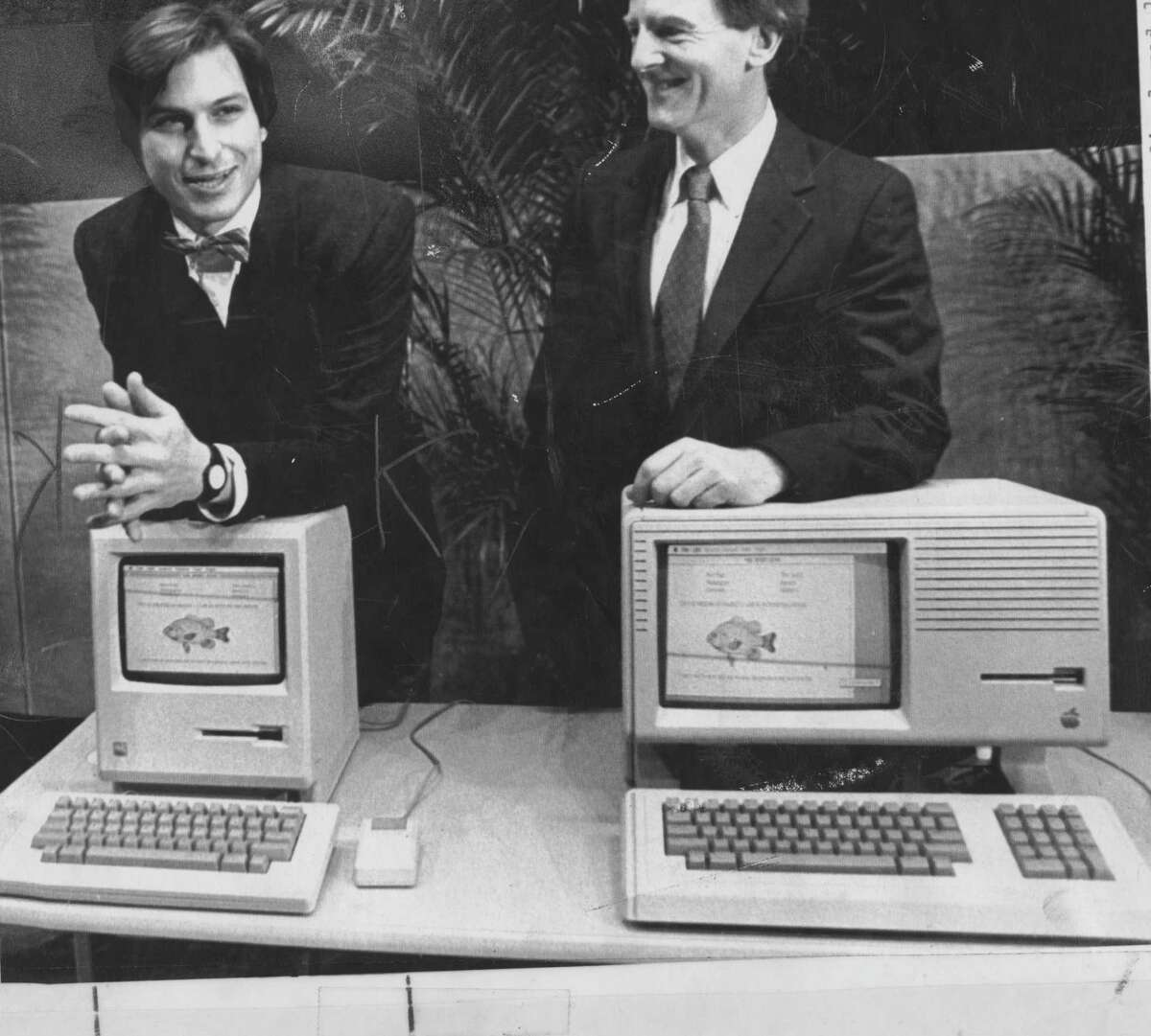 Apple Chairman Steve Jobs with the Macintosh computer, and Apple President John Sculley with the Lisa in 1984. (File Photo)