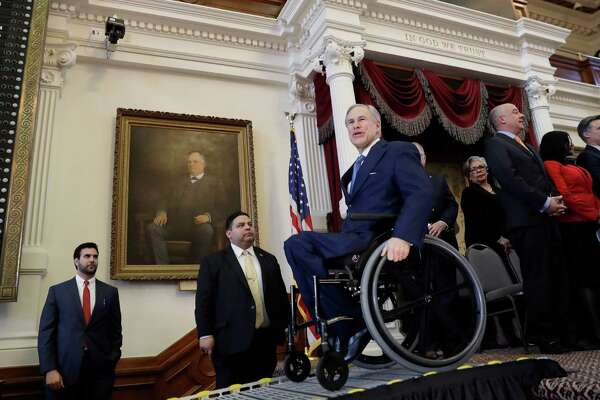 Texas Gov. Greg Abbott, center, uses a ramp to exit the House Chamber at the Texas State Capitol after he addressed the opening session of the 85th Texas Legislative session Tuesday, Jan. 10, 2017, in Austin, Texas. (AP Photo/Eric Gay)