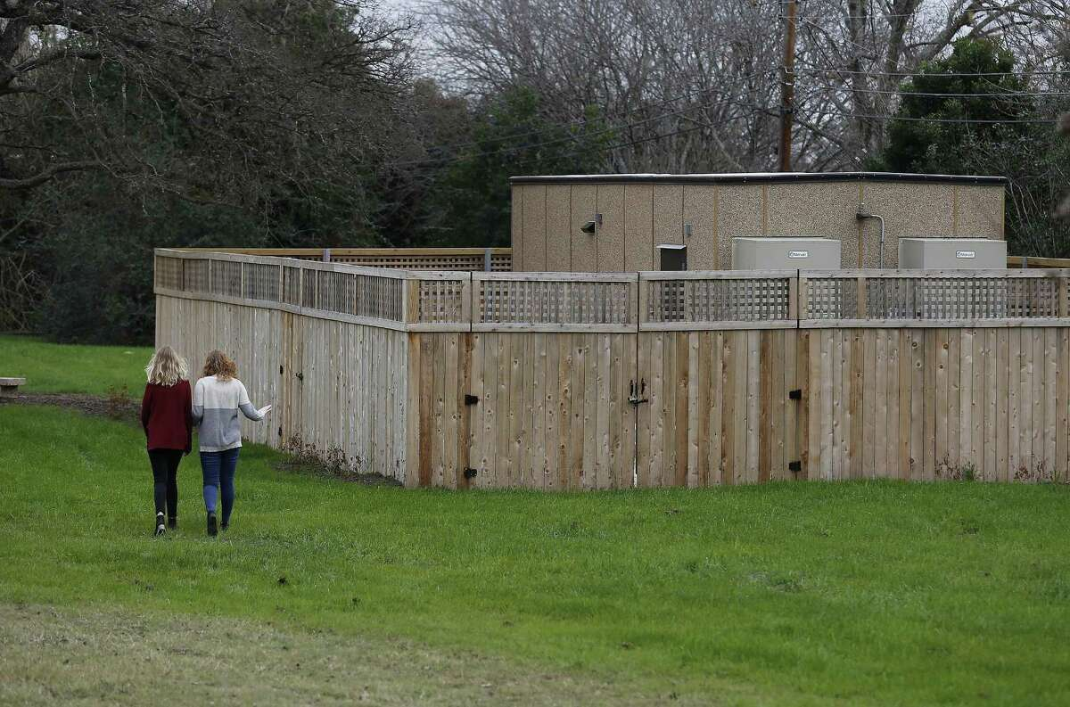 Siblings Anna (left) and Erin Franklin walk by a Google Hut in Haskin Park on Wednesday, Jan. 4, 2017. Their mother and Oak Park Northwood Homeowners Association member Cynthia Franklin is disappointed by the location of the Google Hut which was placed in Haskin Park near her home. She used to be able to look past her chain-link fence and see her kids playing on a playscape in the little park. Now, however, the hut blocks her view. She and others like fellow homeowner John Whitsett are upset and say the city violated its own ordinances in allowing Google to install the network building there. Among other things, they say, it violates rules about fencing, noise and construction. (Kin Man Hui/San Antonio Express-News)