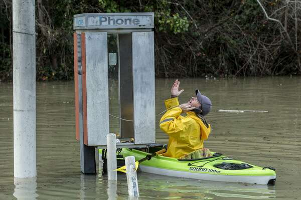 Dustin Coupe is surprised to find out the phone is working as he paddles on a kayak home along River Road during the Russian River flood on Wednesday, Jan. 11, 2017 in Guerneville, Calif.