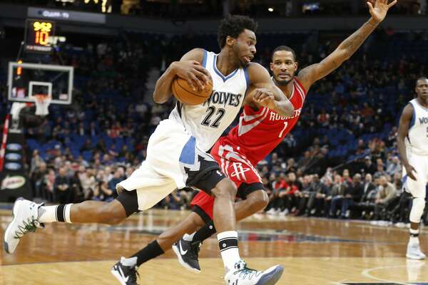 Minnesota Timberwolves' Andrew Wiggins, left, races by as Houston Rockets' Trevor Ariza pursues during the first quarter of an NBA basketball game Wednesday, Jan. 11, 2017, in Minneapolis. (AP Photo/Jim Mone)