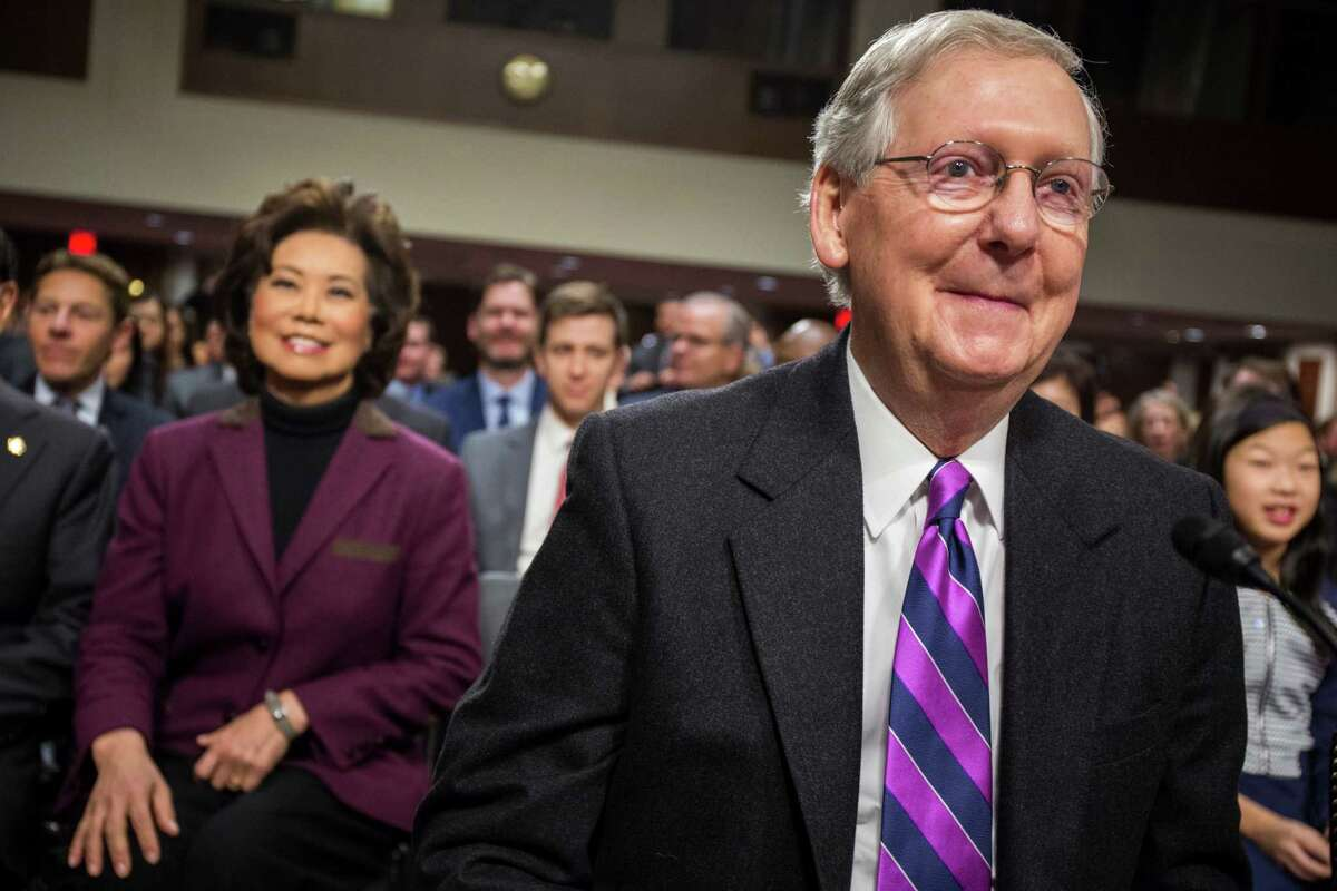 Transportation Secretary-designate Elaine Chao watches as her husband, Senate Majority Leader Mitch McConnell of Ky., arrives on Capitol Hill in Washington, Wednesday, Jan. 11, 2017, to speaks at Chao's confirmation hearing before the Senate Commerce, Science, and Transportation Committee. (AP Photo/Zach Gibson)