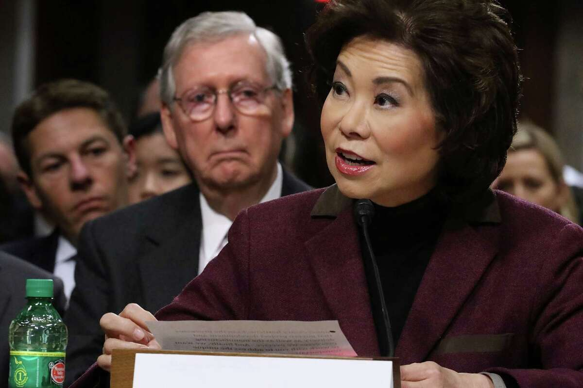 Elaine Chao, transportation secretary nominee, testifies in her confirmation hearing as her husband, Senate Majority Leader Mitch McConnell, looks on.