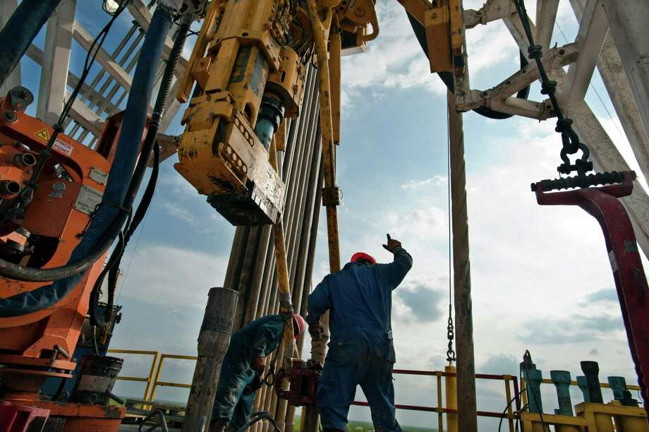 A crew works on a drilling rig in Webb County. Two recent reports point to an improved oil patch outlook. Photo: Eddie Seal / © 2012 Bloomberg Finance LP