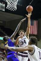 Tyler Davis hoists a shot over LSU's Duop Reath as Texas A&M improved to 1-3 in league play Wednesday night.