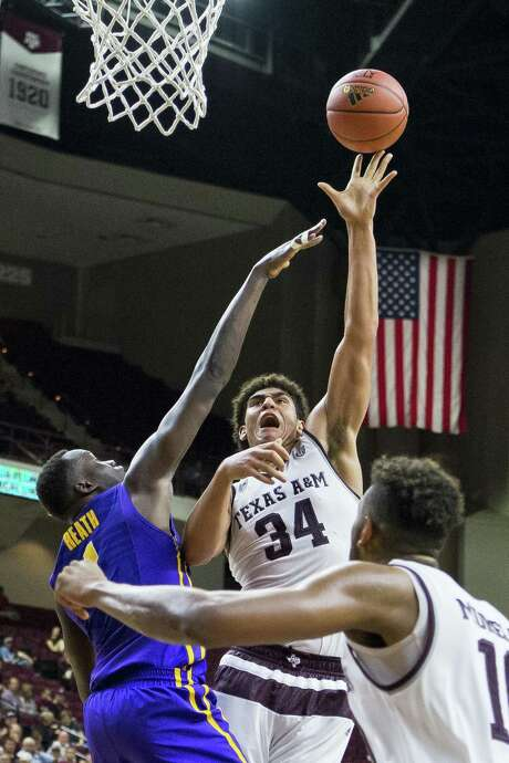 Tyler Davis hoists a shot over LSU's Duop Reath as Texas A&M improved to 1-3 in league play Wednesday night. Photo: Timothy Hurst / Associated Press / The Bryan-College Station Eagle