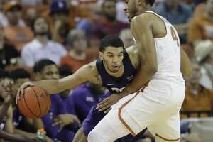TCU guard Kenrich Williams, left, drives around Texas center James Banks (4) during the second half of an NCAA college basketball game, Wednesday, Jan. 11, 2017, in Austin, Texas. TCU won 64-61.(AP Photo/Eric Gay)