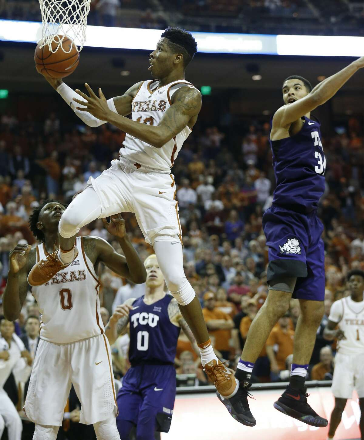 Texas' Kerwin Roach Jr. (12) flies to the basket to attempt a shot against TCU's Kenrich Williams (34) during their game at the Frank Irwin Center in Austin on Wednesday, Jan. 11, 2017. TCU defeated Texas, 64-61.(Kin Man Hui/San Antonio Express-News)