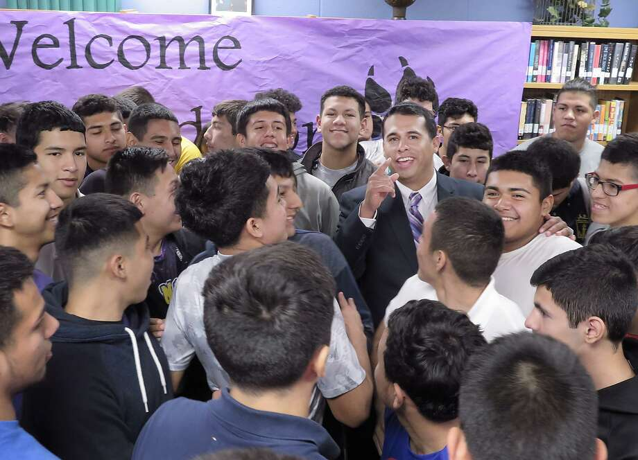 Alfonso Calderon, the new Athletic Coordinator and Head Football Coach for LBJ, is greeted by the Wolf Pack that he will be leading next football season. Calderon was named to the position Wednesday morning at the school's library. Photo: Cuate Santos /Laredo Morning Times / Laredo Morning Times